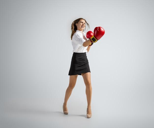 Wanneer het je opwindt. vrouw in kantoorkleding boksen in handschoenen op grijze achtergrond