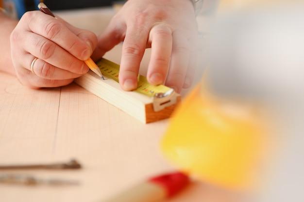 Wapens van arbeider die houten bar meten