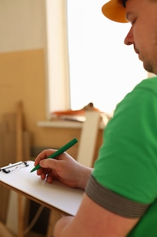 Wapens van arbeider die nota's over klembord met groene pen maken