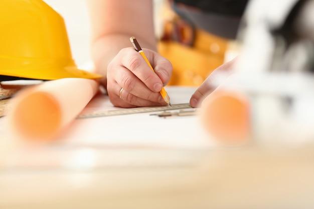 Wapens van arbeider die structuurplan op geschaald document maken