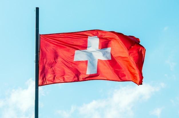 Wapperende kleurrijke vlag van zwitserland op blauwe hemel.
