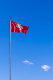 Wapperende vlag van zwitserland op blauwe hemel