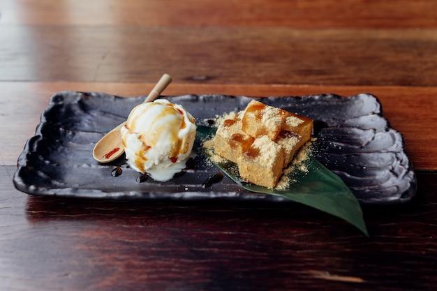 Warabi mochi geserveerd met een bolletje vanille-ijs dat belegt met karamel.