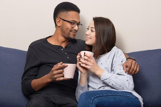 Ware liefde concept. mooi paar knuffelen en poseren op de bank, gekleed in een casual outfit, genieten van samenzijn en gezelligheid