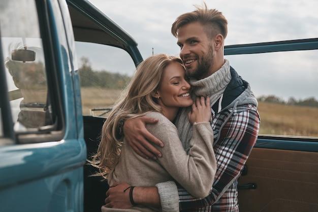 Ware liefde uiten. mooie jonge paar omhelzen en glimlachen terwijl ze buiten staan in de buurt van de retro-stijl minibus