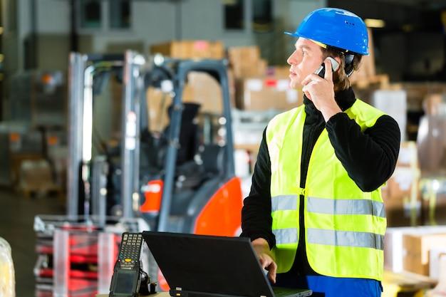 Warehouseman met beschermend vest, scanner en laptop in magazijn bij expeditiebedrijf met behulp van een mobiele telefoon
