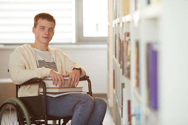 Warm afgezwakt portret van een jonge man met rolstoel op school terwijl hij in de bibliotheek is verlicht door zonlicht
