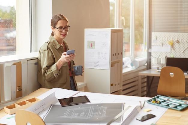 Warm afgezwakt portret van jonge vrouw genieten van koffie en smartphonescherm kijken tijdens koffiepauze in kantoor,