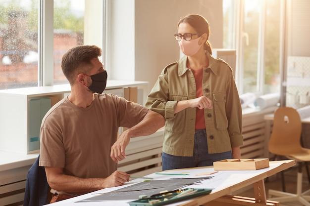 Warm afgezwakt portret van twee collega's die maskers dragen die ellebogen stoten als contactloze begroeting in post pandemisch kantoor