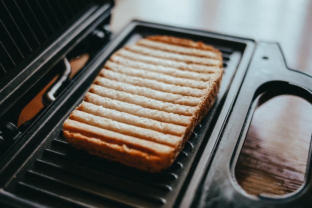 Warm broodje met een gouden korst en strepen, gekookt op de elektrische grill