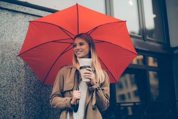 Warm en beschermd voelen. aantrekkelijke jonge lachende vrouw met paraplu en koffiekopje terwijl ze op straat staat