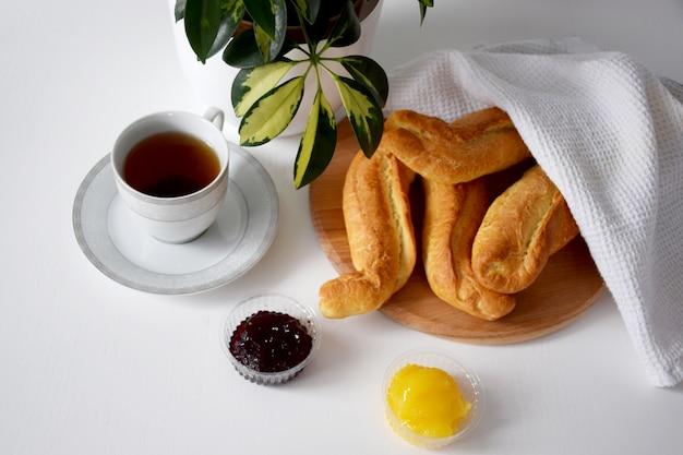 Warm gebakken broodjes onder witte theedoek op houten snijplank, honing en jam op witte tafel voor ontbijt