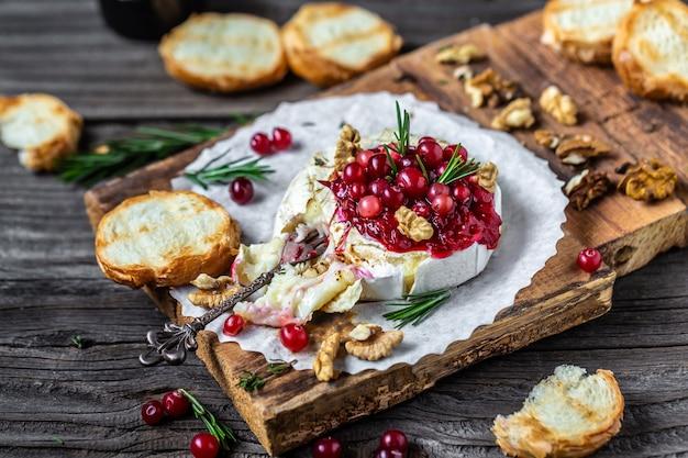 Warm gebakken camembert met verse rozemarijn, cranberrysaus en stokbrood op houten tafel.