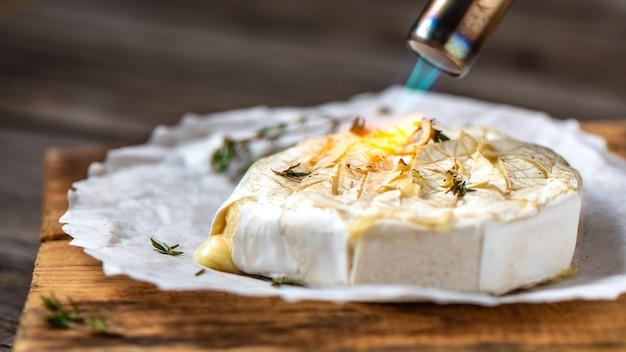 Warm gebakken of gebakken gegrilde camembert of brie kaas met bessensaus of jam.