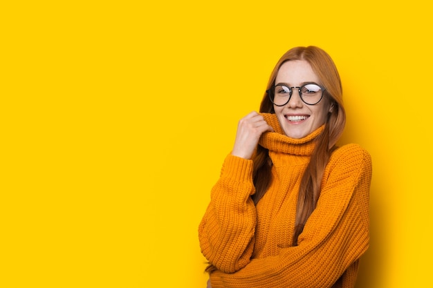 Warm geklede blanke vrouw met gember haar en sproeten is poseren in een trui op een gele muur met vrije ruimte