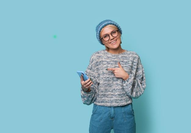 Warm geklede vrouw poseert op een blauwe muur en wijst naar haar telefoonscherm glimlachend in de camera