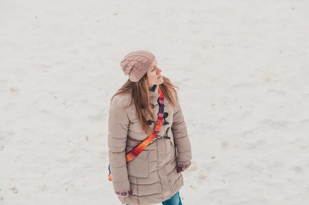 Warm gekleed meisje dat in de winter op de bevroren rivier loopt