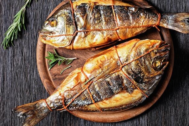 Warm gerookte goudbrasem, orata vis op een houten ronde snijplank op een donkere houten tafel met vork, rozemarijn en peperkorrel, horizontale weergave van bovenaf