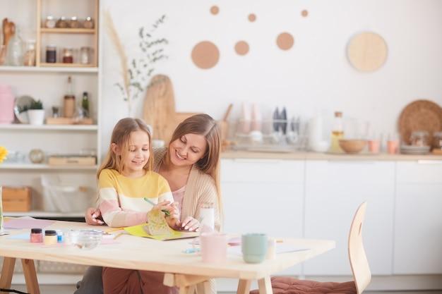 Warm-gestemde portret van gelukkige moeder knuffelen dochtertje tijdens het tekenen van afbeeldingen aan de houten keukentafel, kopie ruimte