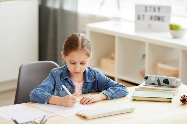 Warm-gestemde portret van schattig klein meisje huiswerk aan bureau tijdens het studeren thuis in gezellig interieur, kopie ruimte