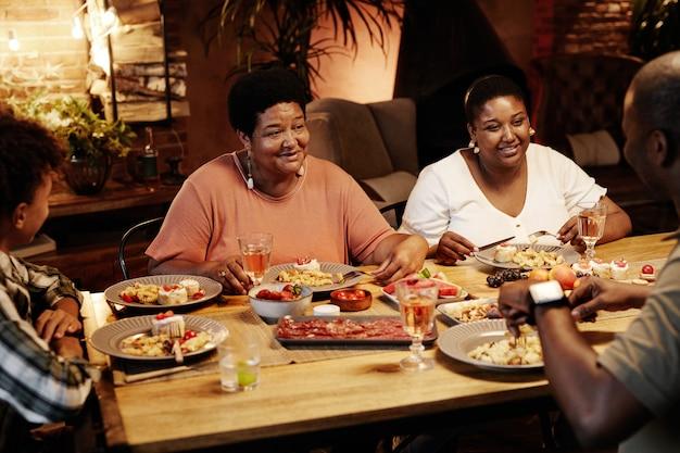 Warm getint portret van een gelukkige afro-amerikaanse familie die 's avonds samen binnen geniet van het diner