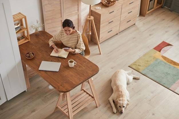 Warm getinte hoge hoek portret van moderne jonge vrouw die werkt op kantoor aan huis met hond die bij haar wacht in een gezellig interieur, kopieer ruimte