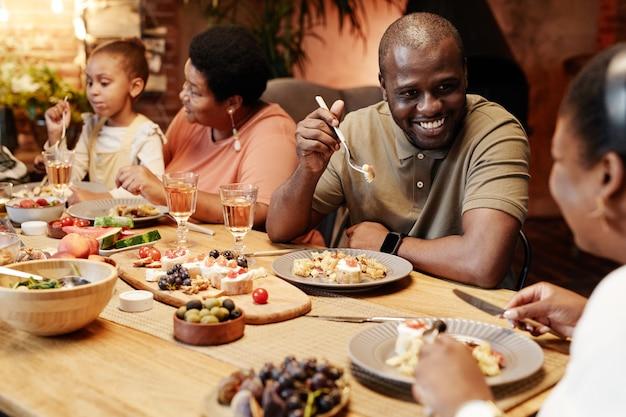 Warm getinte portret van gelukkige afro-amerikaanse familie genieten van diner samen buiten met focus op ...