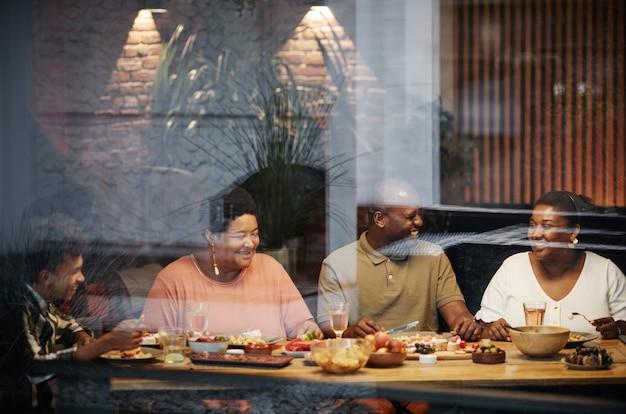 Warm getinte portret van gelukkige afro-amerikaanse familie genieten van diner samen op terras achter glas...