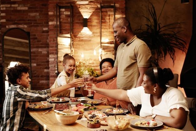 Warm getinte portret van gelukkige afro-amerikaanse familie rammelende glazen en roosteren terwijl u geniet van din...