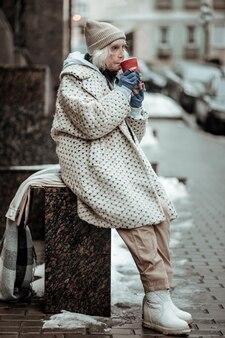 Warm houden. triest senior vrouw met zeer hete thee terwijl ze op straat stond