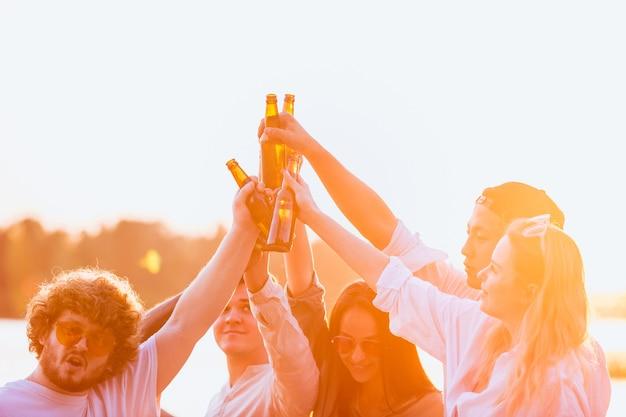 Warm licht groep vrienden rammelende bierglazen tijdens picknick op het strand in de zon