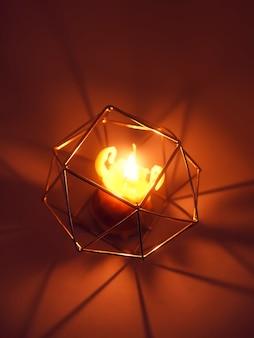 Warm licht van handgemaakte natuurlijke bijenwas stervende kaars in een kandelaar op houten schijfje.