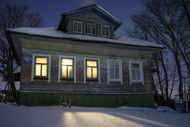 Warm licht van ramen, gezellig oud russisch dorpshuis in het bittere koude winternachtlandschap met sneeuwsterrenrook uit oven