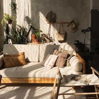 Warm modern interieur in boho-stijl. bankstel, kussens, kamerplanten, tapijt en decoraties tegen betonnen muur