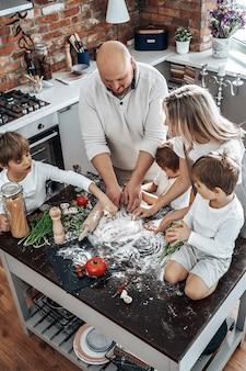 Warm portret van een liefdevol en gelukkig gezin dat samen iets van deeg kookt. drie jongens met hun ouders in de keuken.