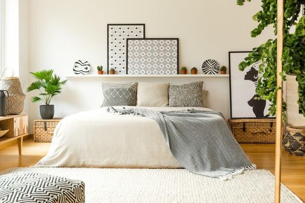 Warm slaapkamerinterieur met een comfortabel bed, deken en kussens met patroon, planten en moderne graphics