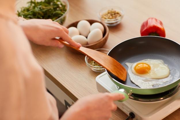 Warm-toned close-up van onherkenbare jonge vrouw die eieren op koekenpan kookt tijdens het bereiden van een gezond ontbijt in de ochtend