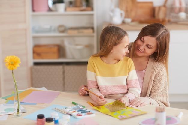 Warm-toned portret van gelukkige moeder knuffelen dochter tijdens het schilderen van foto's aan de houten keukentafel, kopie ruimte