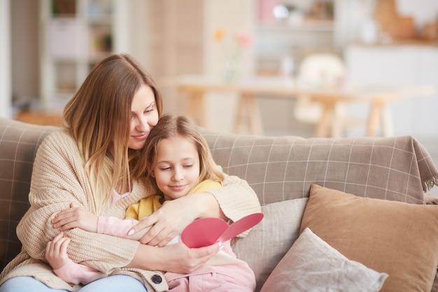 Warm-toned portret van glimlachende moeder omhelst dochter tijdens het lezen van handgemaakte kaart op moederdag, kopieer ruimte