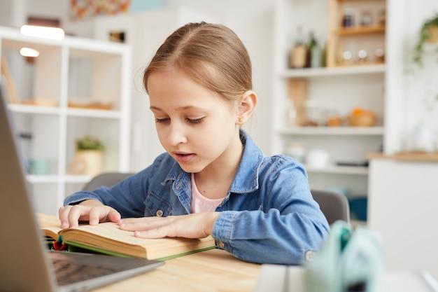 Warm-toned portret van schattig klein meisje tekst lezen op laptop camera tijdens het studeren online thuis in gezellig interieur, kopieer ruimte