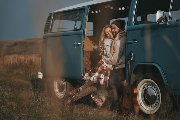 Warm voelen in zijn armen. knappe jonge man omhelst zijn mooie vriendin en lacht zittend in blauwe retro-stijl minibusje