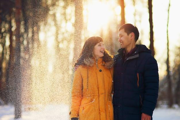 Warm winter portret van jonge sex tussen verschillendre rassen glimlachend paar op een wandeling in het bos