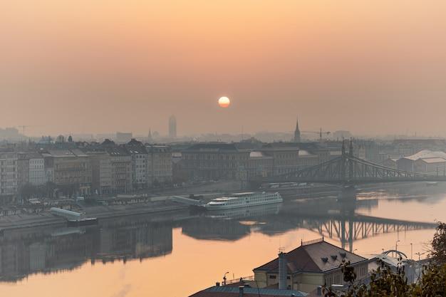 Warm zonsopgangbeeld van boedapest met een liberty-brugmening en bezinningen in de rivier van donau