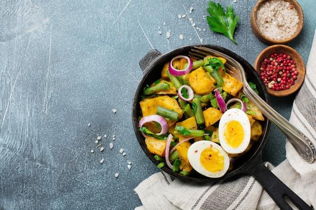 Warme aardappelsalade met groene bonen, paprika, peterselie, eieren en rode ui in koekenpan op grijze betonnen tafel. selectieve aandacht. bovenaanzicht. kopieer ruimte.