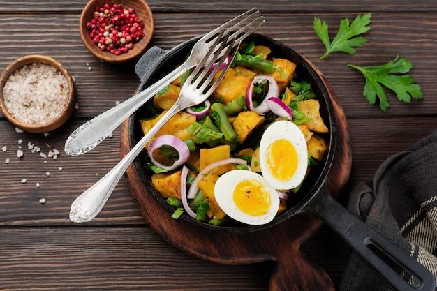 Warme aardappelsalade met sperziebonen, peper, peterselie, eieren en rode ui in koekenpan op oude houten tafel. selectieve aandacht. bovenaanzicht. kopieer ruimte.