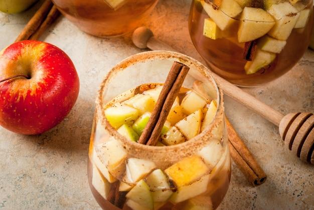 Warme appelcider met stukjes fruit en kaneel