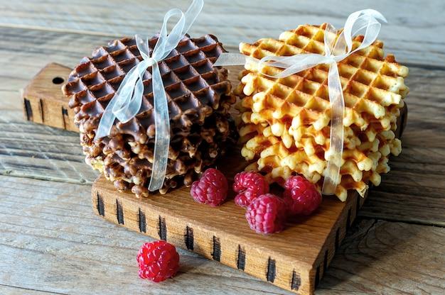Warme belgische wafels met frambozen op snijplank.