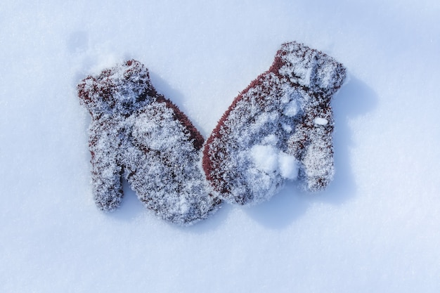Warme bruine kinderwanten op sneeuwoppervlak.
