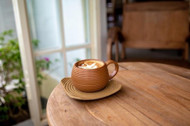 Warme bruine kop cappuccino op houten tafel achtergrond in café