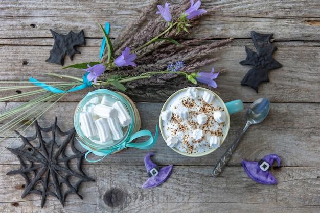Warme cappuccino met marshmallows en schuim in een lichtblauwe beker met bloemen. op halloween.